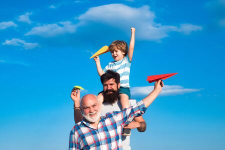 Happy three generations of men have fun and smiling on blue sky background. Father and son playing outdoors. Airplane ready to fly. Cute son with dad playing outdoor.