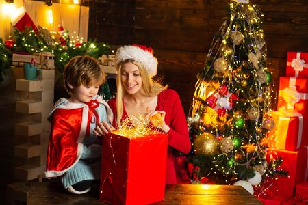 Family holiday. Cozy evening at home. Mom and kid play together christmas eve. Happy family. Mother and little child boy son friendly family having fun. Family having fun at home christmas tree