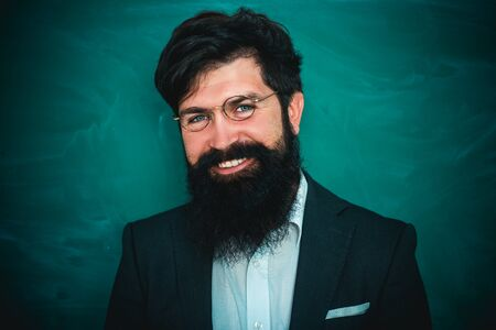 Teachers challenges and inspires. Bearded professor at school lesson at desks in classroom. Young bearded teacher near chalkboard in school classroom.