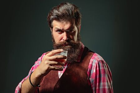 Confident well-dressed man with glass of whisky. Man with beard holds glass brandy. Barman or Bartender serves cognac.
