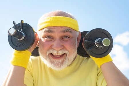 Happy Senior sport man exercising with lifting dumbbell on blue sky background. Isolated, copy space.