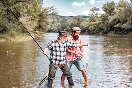 Fly rod and reel with a brown trout from a stream. Man fishing. Fly fisherman using fly fishing rod in beautiful river. Father and son relaxing together.