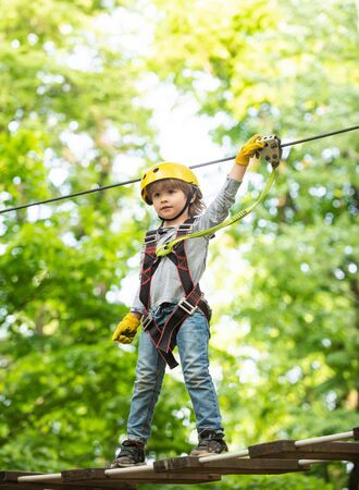 Child boy having fun at adventure park. Carefree childhood. Child climbing on high rope park. Happy Little child climbing a tree. Go Ape Adventure.