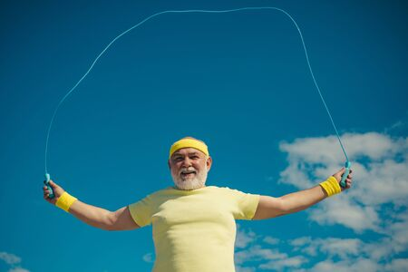 Portrait of old man exercising with jumping rope on blue sky background. Freedom retirement concept. Portrait of healthy senior sport man. Be in motion. Sporting. Stok Fotoğraf
