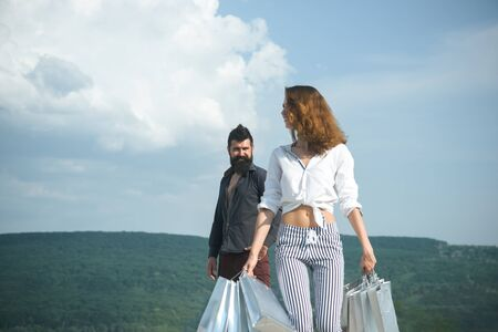 bearded man with happy woman hold shopping bag. successful shopping. sense of freedom. couple in love. present packages. family holiday. summer fashion. spring. We love shopping. Pleasant price