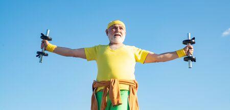 Senior man exercising on blue sky. Senior male is enjoying sporty lifestyle.