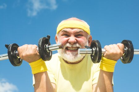 Senior sportman exercising with lifting dumbbell on blue sky background. Isolated, copy space.