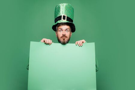 Shocked and happy male face. Happy Saint Patricks day. Hipster in leprechaun hat and costume with wide open eyes celebrating Saint Patricks day.