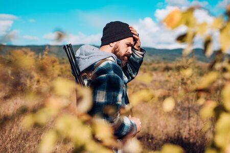 Poacher with Rifle Spotting Some Deers. Hunter in the fall hunting season. Hunter with shotgun gun on hunt. Mountain hunting.