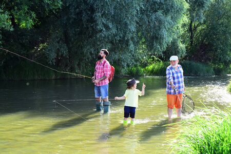 Grandfather, father and son are fly fishing on river. 写真素材