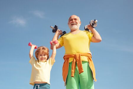 Active family enjoy sport and fitness. Funny old senior man and kid boy with dumbbells. Grandfather and child do morning exercise.