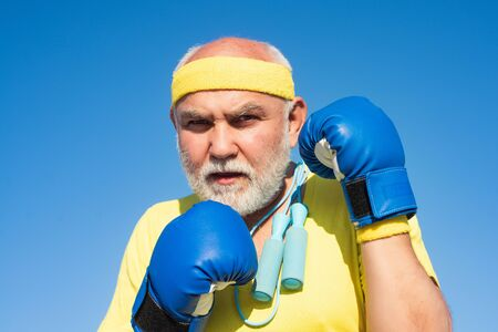 Older man boxing - close up portrait. Handsome elderly man practicing boxing kicks. Senior sport man wearing boxing gloves. Funny bearded man standing in boxing pose. Fighter.