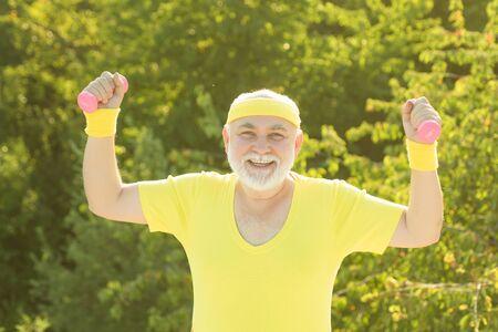 Senior sportman lifting dumbbells. Elderly man workout. Like sports. Reklamní fotografie