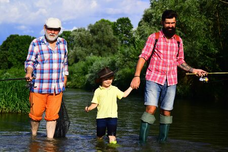 Grandfather, father and son are fly fishing on river. Fly fisherman using fly fishing rod in river. 3 men fishing on river in summer time.