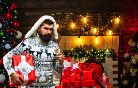 Bearded man in Christmas sweater. Santa Claus wishes Merry Christmas. Gift emotions. Christmas Celebration holiday.
