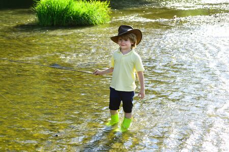 Cute little boy fishing on pond. Young man fly fishing. Photo of little boy fishing. Boy in yellow shirt with a fishing rod by the river.