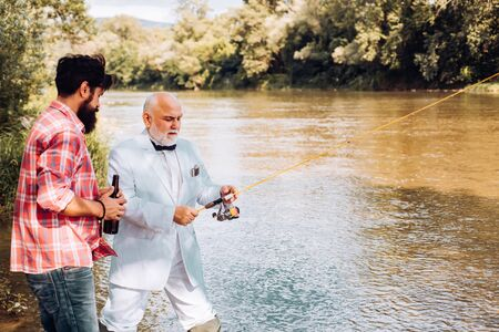 Fly fishing is most renowned as a method for catching trout grayling and salmon. Happy father and son fishing in river holding fishing rods. 写真素材