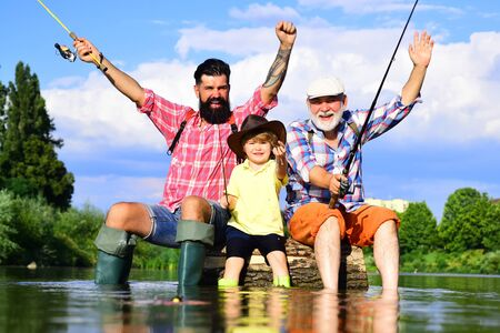 Grandfather and grandchild. Portrait of happy little son, father and grandfather - three generations of men fishing on river.