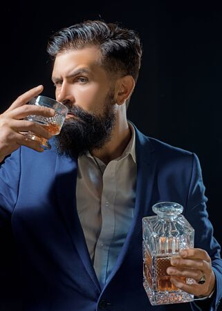Sipping whiskey. Man Bartender holding glass of whisky. Bearded handsome man holding glass of whiskey. Sipping finest whiskey.