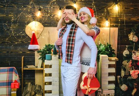 Surprise for sweetheart. Merry christmas and happy new year. Christmas gifts. Man handsome with gift box surprise for girlfriend. Man hipster give gift to girl christmas decorations. Guess who Stock Photo