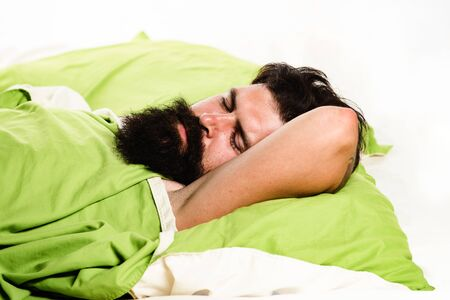 Violations of sleep and wakefulness. Young man sleeping on soft pillows in bed at home. Man bearded hipster having problems with sleep. Stock Photo