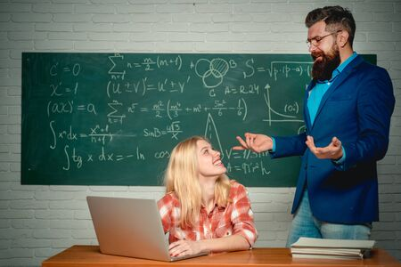 Education. Teacher helping young student with lesson. Tutoring. Student and teacher sitting at desks in classroom. University seminar. Ready for school. Students preparing for university exams.