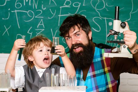 Education. Science. Childhood education concept. School concept. Teacher teaches a student to use a microscope. Man teaches child. Cheerful smiling little boy and teacher having fun against blue wall