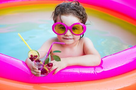 Smiling cute little boy in sunglasses in pool in sunny day with colorful tropical cocktail. Little child boy relaxing in resort swimming pool and drinking cocktails. Imagens