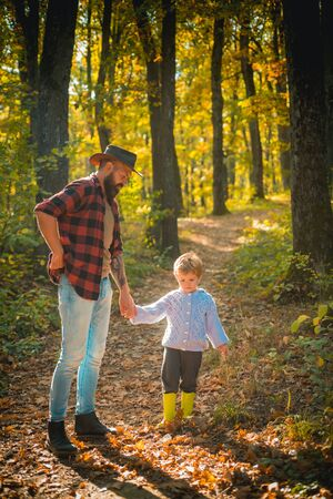 Family values. Wanderlust concept. Hipster bearded dad with cute son spend time together in forest. Family time. Family leisure. Brutal bearded man and little boy enjoy autumn nature. Explore nature