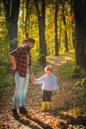 Wartości rodzinne. Koncepcja wędrówki. Hipster brodaty tata z uroczym synem spędzają razem czas w lesie. Czas dla rodziny. Wypoczynek rodzinny. Brutalny brodaty mężczyzna i mały chłopiec cieszą się jesienną przyrodą. Poznawać naturę