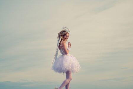 Cupido querubín adolescente. Tarjeta de felicitación de arte festivo. Chica inocente con alas de ángel de pie con arco y flecha contra el cielo azul y nubes blancas. Tarjeta de amor. Foto de archivo