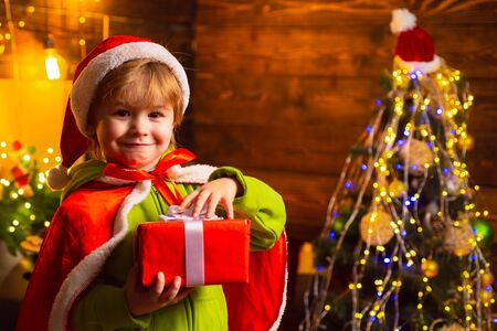 Home filled with joy and love. Merry christmas and happy new year. Family day christmas. Gifts and surprises. Cute little child boy play near christmas tree. Kid enjoy winter holiday at home
