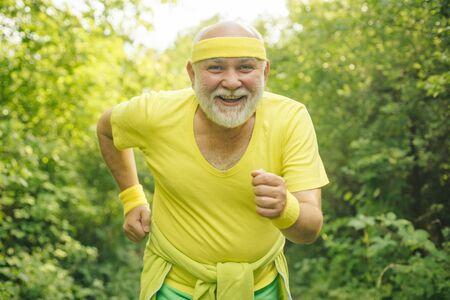 Smiling happy elderly man running. Senior man is doing sport outdoors. Senior man workout in rehabilitation center. The old and young sportsmen running on the road. Reklamní fotografie - 128604873