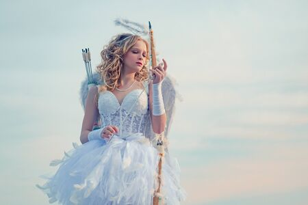 Lovely child. little Cupid girl aiming at someone with an arrow of love. Bow and arrow. Little goddess with white wings alone on blue sky background. Cherub girl Фото со стока