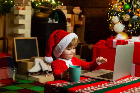 Smart toddler surfing internet. Little boy santa hat and costume. Boy child with laptop near christmas tree. Buy christmas gifts online. Christmas shopping concept. Gifts service. Santa little helper Stock Photo