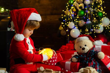 Boy child play near christmas tree. Merry and bright christmas. Childhood activity and game. Lovely baby enjoy christmas. Family holiday. Childhood memories. Santa boy celebrate christmas at home
