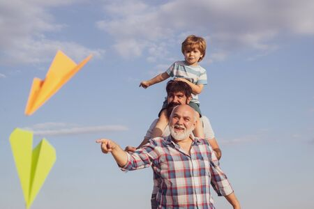 Cute child hugging his father and grandfather. Happy family. Airplane ready to fly. Happy three generations of men have fun and smiling on blue sky background. Weekend family play. 写真素材