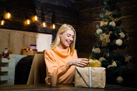 Christmas time. Celebration. Fashion portrait of girl indoors with Christmas tree. True Emotions. Happy emotion. Christmas decorations and gift box on wooden background. Фото со стока
