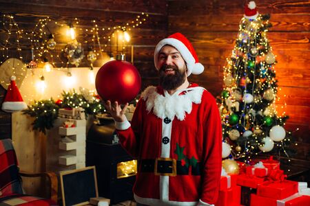 Fashion portrait of handsome man indoors with Christmas tree. Styling Santa hipster with a long beard posing on the Christmas wooden background. Фото со стока
