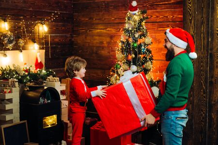 Father and son having fun near Christmas tree indoors. New year Christmas concept. Little Santa and old bearded Santa gifting gift. Wish you merry Christmas. Фото со стока