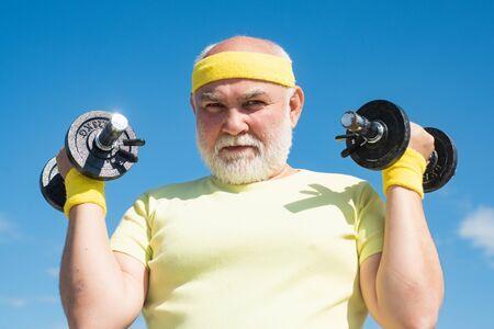 Senior sportman exercising with lifting dumbbell on blue sky background. Isolated, copy space. Senior male is enjoying sporty lifestyle.
