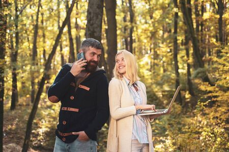 Happy autumn couple. Business couple - woman browsing Internet on a notebook, man using mobile phone outdoors. Autumn outdoor portrait of beautiful happy girl and bearded man walking in park. Фото со стока
