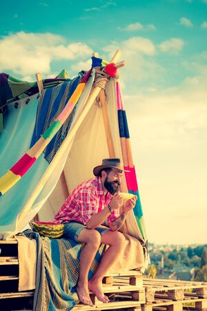 Bearded man in hovel on sky background. Shelter of branches. Love makes a cottage a castle. Homemade tent glows under a clouds.