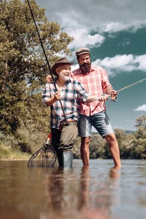 Happy family concept - father and son together. Fly fishing. Generations ages: grandfather and father. Generations men. 写真素材 - 128605043
