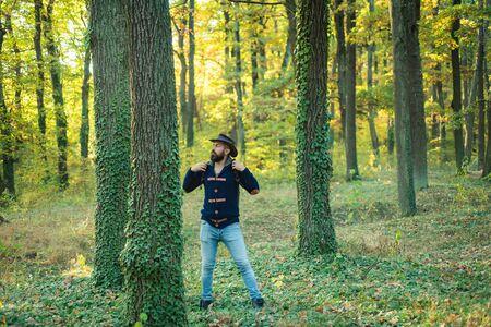 Porträt des gutaussehenden Mannes, der draußen geht. Mann mit Blättern im Freien. Gut aussehender Mann, der im Park spazieren geht und die schöne Herbstnatur genießt.
