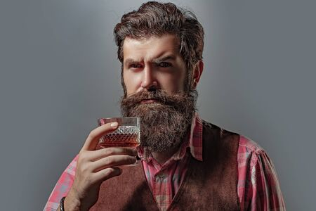 Serious unhappy sad man pouring vodka while having alcohol addiction. Confident well-dressed man with glass of whisky.