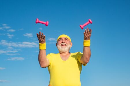 Freedom retirement concept. Portrait of healthy happy smile senior. Health club or rehabilitation center for elderly aged pensioner. Senior sport man lifting dumbbells in sport center.