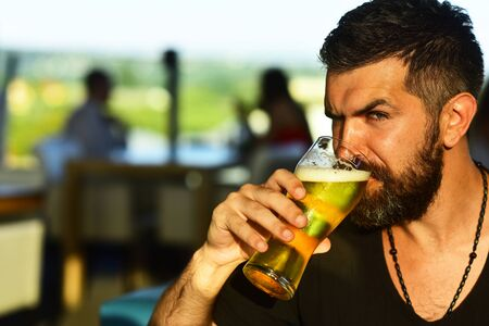 Portrait of handsome young man tasting a draft beer. Pub is relaxing place to have drink and relax. Cheerful young man holding glass of beer and looking at camera.