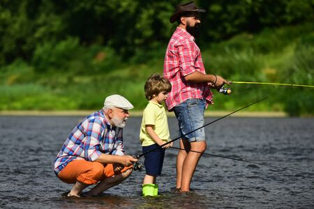 Portrait of happy little son, father and grandfather - three generations of men fishing on river. Family fishermen fishing with spinning reel. 写真素材 - 128605066