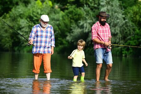 Fly fisherman using fly fishing rod in river. Happy people family have fishing and fun together. Senior man fishing with son and grandson. 写真素材
